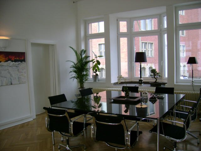 Großer Besprechungstisch mit acht schwarzen Stühle