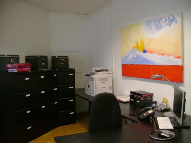 Schreibtisch mit schwarzen Aktenschränken im Hintergrund