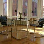 Besprechungstisch aus Glas, zwei schwarze Stühle